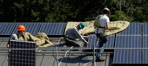 Workers install rooftop solar panels