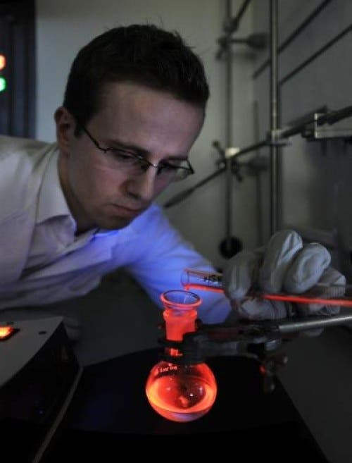 Michał Maciejczyk, a doctoral student at the IPC PAS, demonstrates record efficient luminescence of europium complexes with phosphine oxide co-ligands -- new chemicals developed at the Institute of Physical Chemistry of the Polish Academy of Sciences in Warsaw. IPC PAS, Grzegorz Krzyżewski Image Credit: